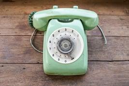 green-vintage-telephone-on-brown-wood-desk-background_BwJxPaeu3Gx